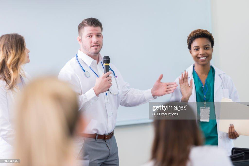Médico introduz colega durante seminário da saúde : Foto de stock