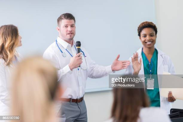 Doctor introduces colleague during healthcare seminar