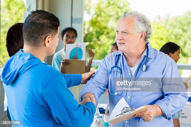 Doctor introducing himself to patient at temporary free shot clinic