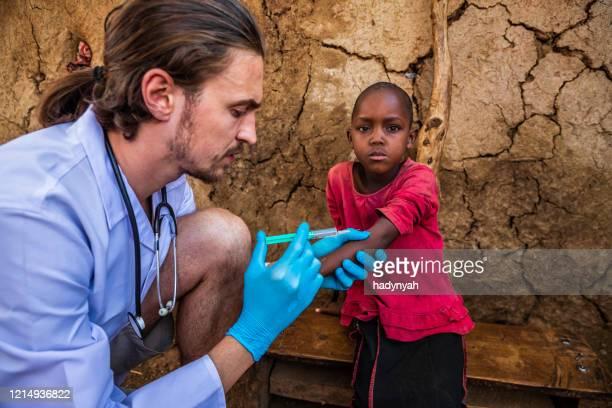 医師は小さな村、ケニアで小さなアフリカの女の子に注射をしています - 発展途上国 ストックフォトと画像