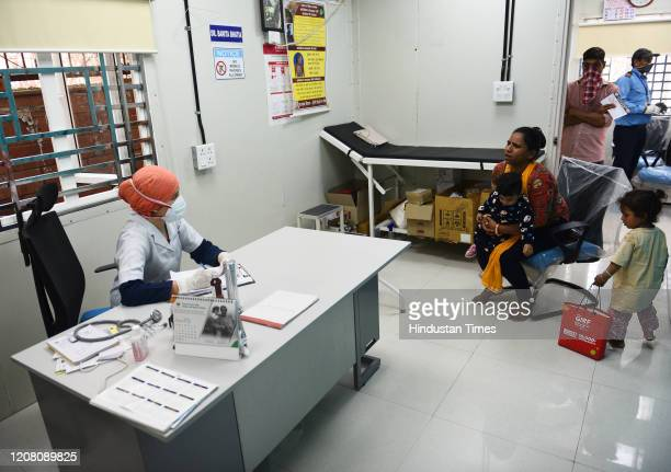 A doctor is seen maintaining social distance with her patients at a mohalla clinic during the second day of lockdown imposed by the state government...