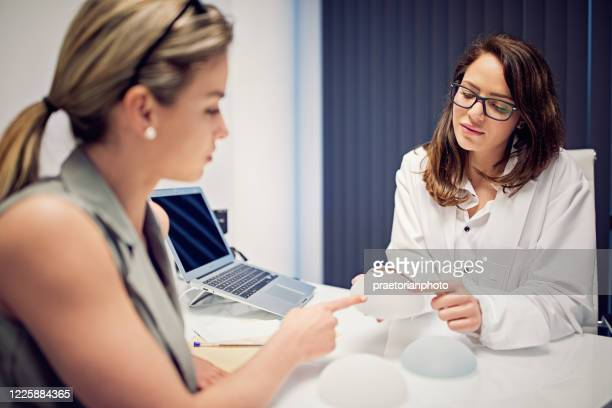 doctor is showing breast implants to young woman in beauty treatment clinic - best bosom stock pictures, royalty-free photos & images