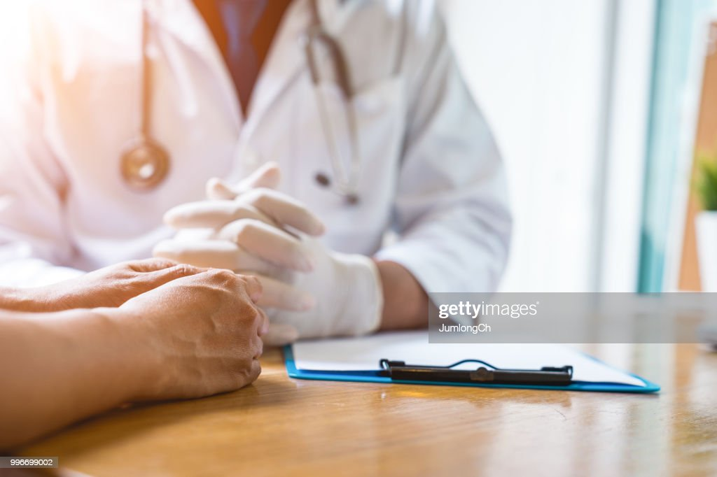 A doctor is working in the hospital, he is wearing a brown stethoscope and he is investigating the illness of the patient. : Stock Photo