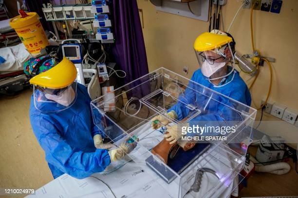 Doctor Jana du Plessis and Doctor Anele Mtanjana demonstrate how to use an intubox for worker safety designed at the Charlotte Maxeke Hospital in...