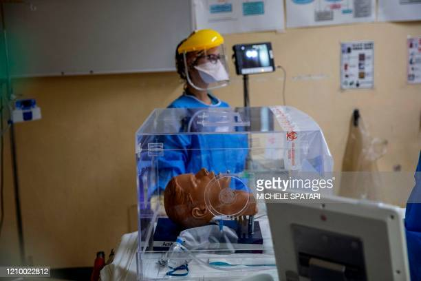 Doctor Jana du Plessis demonstrates how to use an intubox for worker safety designed at the Charlotte Maxeke Hospital in Johannesburg on April 15...