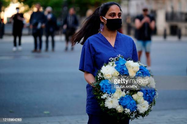 """Doctor joins a silent protest during a national """"clap for carers"""" to show thanks for the work of Britain's NHS workers and other frontline medical..."""