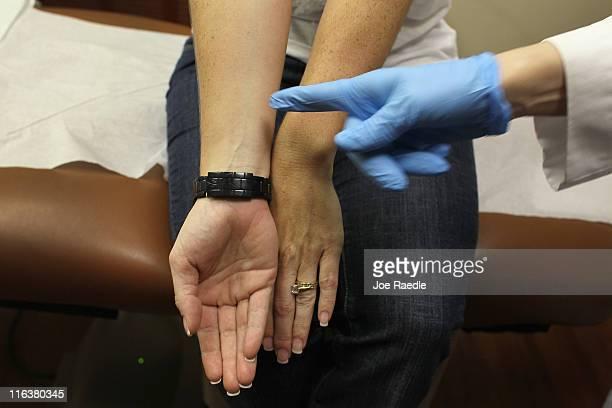 Doctor Jonette Keri, Dermatologist University of Miami School of Medicine, displays the underside of Amy Rey's arm in contrast to the top side to...