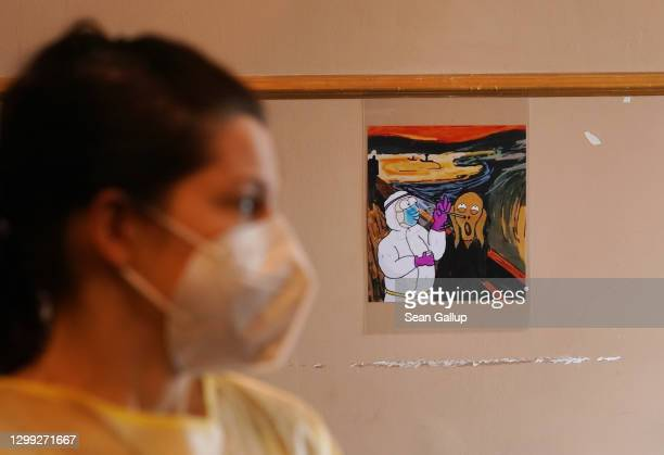 """Doctor Jule Teufel waits for the next person seeking a COVID-19 test as a reworked version of Edvard Munch's """"The Scream,"""" which shows Homer Simpson..."""