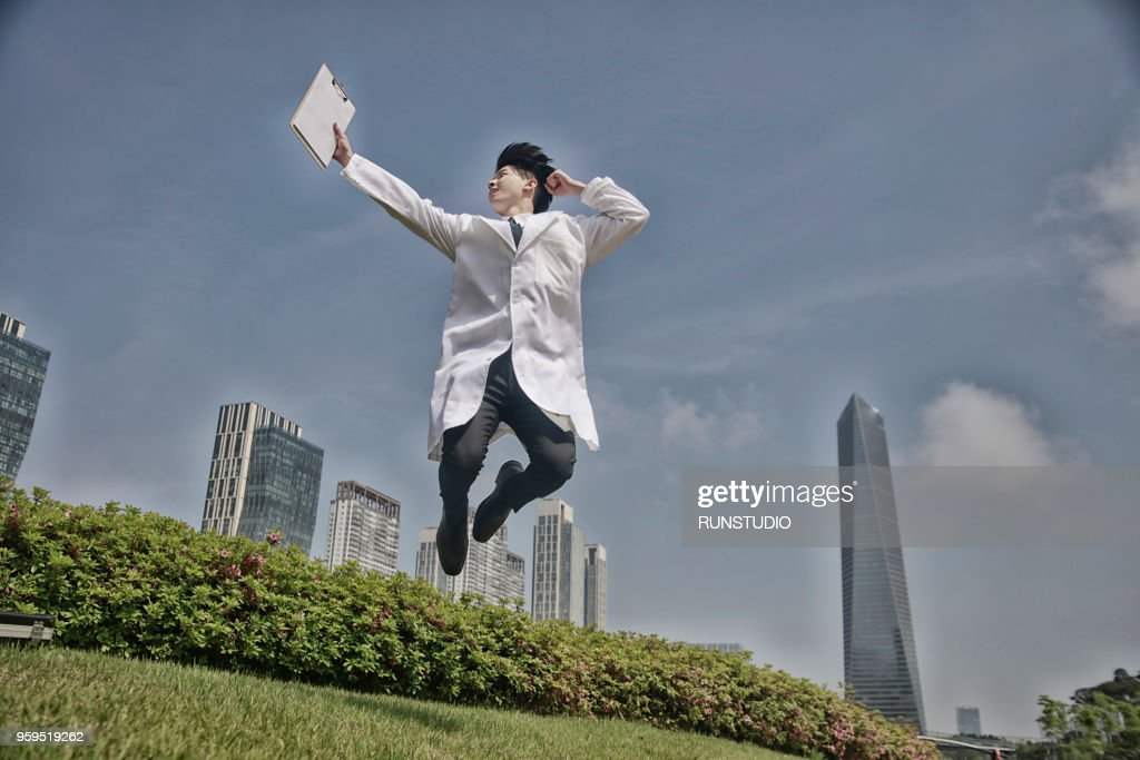 Doctor jumping up with clipboard : Stock-Foto