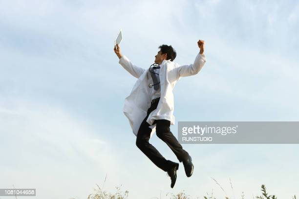 doctor jumping with digital tablet - laborkittel stock-fotos und bilder