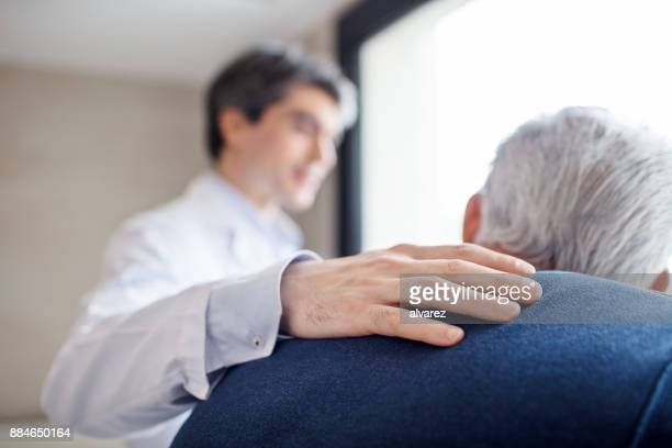 doctor keeping hand on senior man's back - responsibility stock pictures, royalty-free photos & images