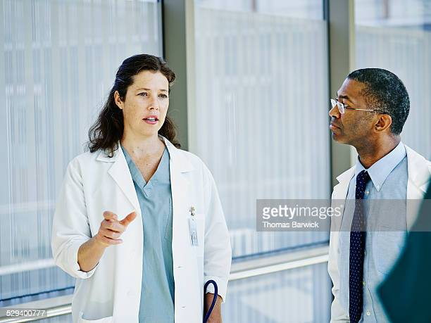 doctor leading discussion with colleagues - leanintogether stock pictures, royalty-free photos & images