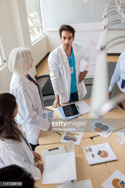 doctor leads staff meeting - pamphlet stock pictures, royalty-free photos & images