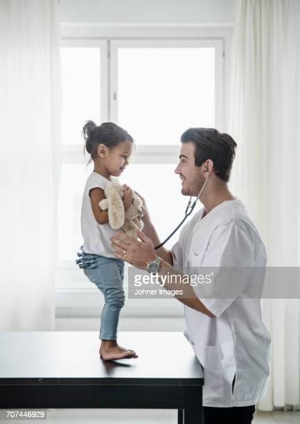 Doctor listening girls heartbeat