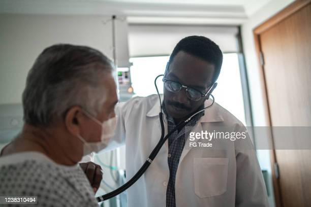 doctor listening patient's heartbeat at hospital room - cardiologist stock pictures, royalty-free photos & images