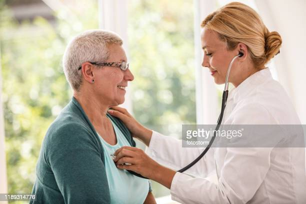 doctor listening patient's heartbeat - heart disease stock pictures, royalty-free photos & images