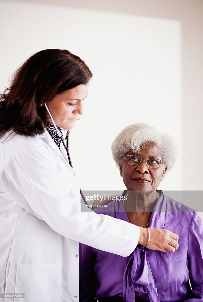 Doctor listening to a senior patient's heart : Foto de stock