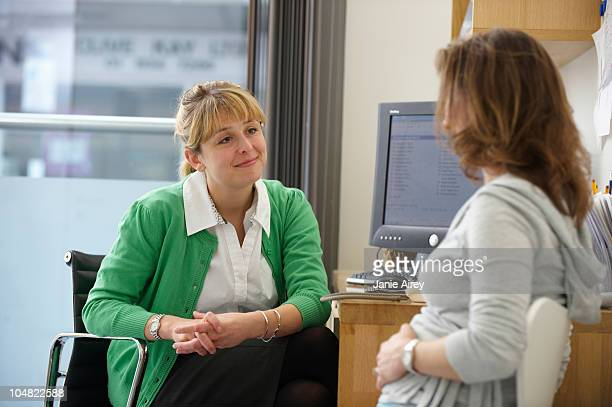 Doctor listening to female patient