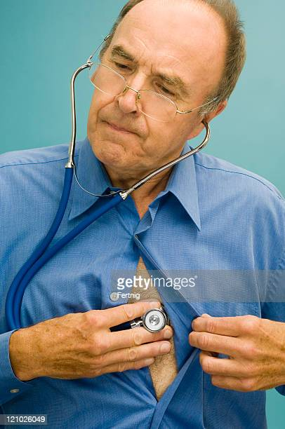 doctor listening to his own chest with a stethoscope - hypochondria stock photos and pictures