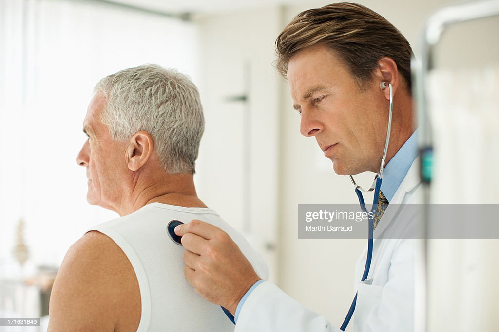 Doctor listening to man's breathing in doctor's office : Stock Photo