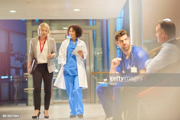 doctor listening to sales rep in hospital corridor - hospital imagens e fotografias de stock