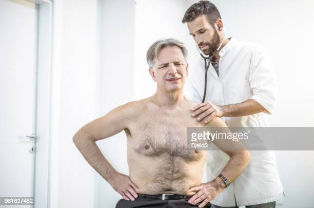 doctor listening to senior male patient's lungs. - cardiovascular system stock photos and pictures