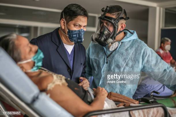 Doctor listens to a nurse about a woman infected by coronavirus as she arrives at the Gilberto Novaes Municipal Field Hospital on May 27, 2020 in...