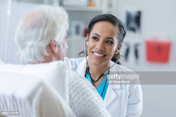 doctor listens to patient's heart in the hospital - emergency medicine stock pictures, royalty-free photos & images
