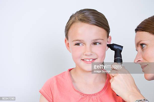 Doctor looking at girls ear