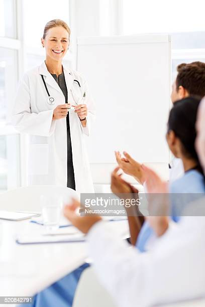 Doctor Looking At Medical Team Applauding For Her