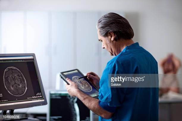 doctor looking at mr scan on portable computer - portable information device imagens e fotografias de stock
