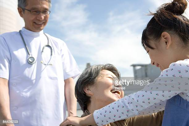 Doctor looking at senior woman and girl hugging