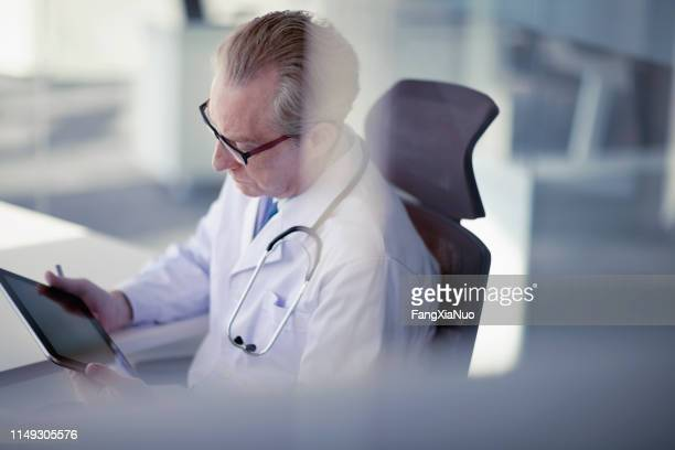 doctor looking at tablet computer in office - test results stock pictures, royalty-free photos & images