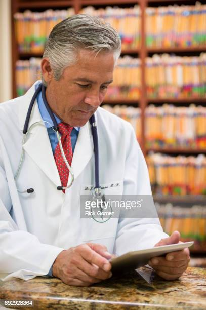 Doctor looking at tablet in office.