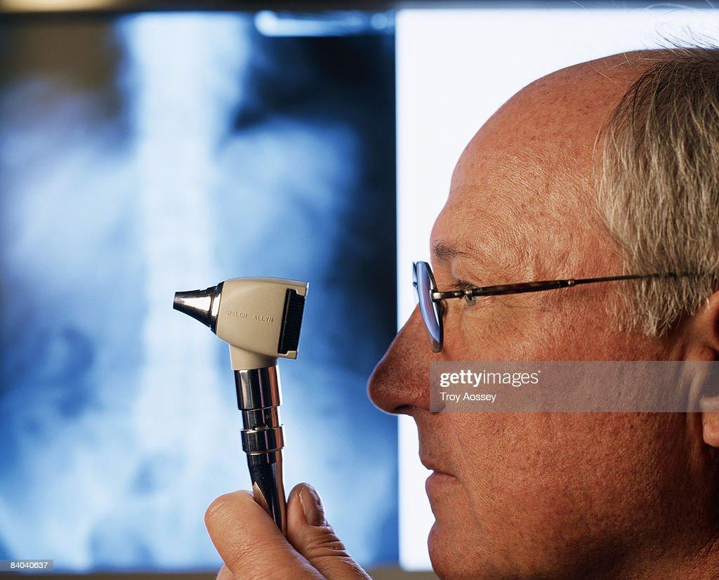 Doctor looking at X-ray holding medical tool : Bildbanksbilder