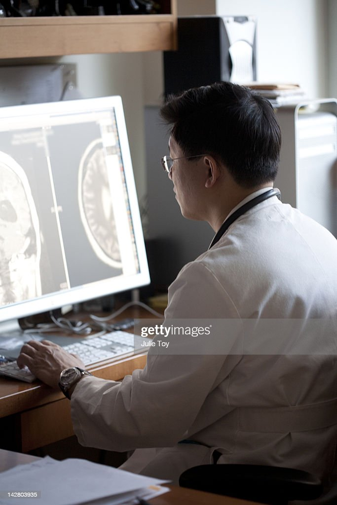 Doctor looking at x-ray on computer : Stock Photo
