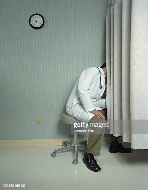 Doctor looking behind curtain during exam