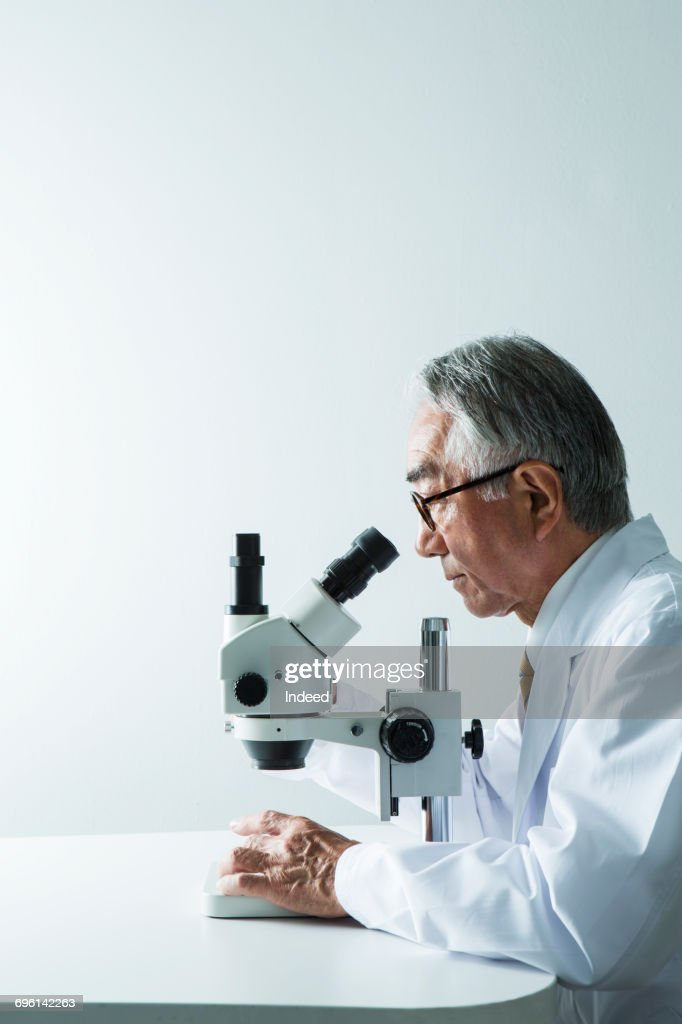 Doctor looking through object using microscope : Stock Photo