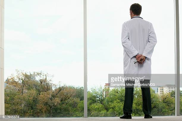 Doctor looking through window