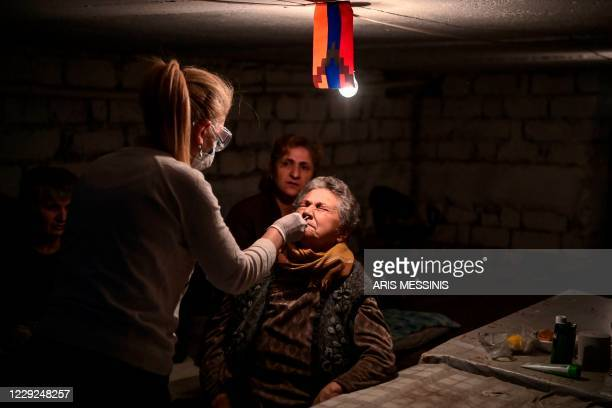TOPSHOT Doctor Lucine Tovmasyan swabbs the nose of an elderly woman as she adminsters a novel coronavirus Covid19 test in the city of Stepanakert on...