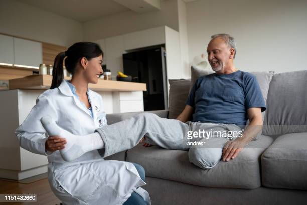 doctor making a home visit to a disabled senior patient - diabetic amputation stock pictures, royalty-free photos & images