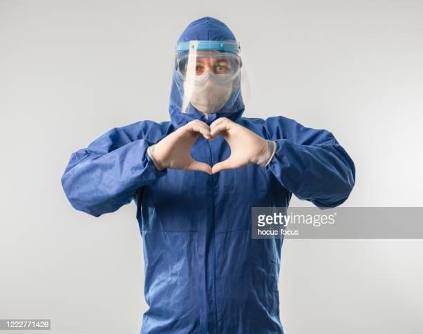 doctor making heart shape and sending love during coronavirus covid 19 novel corona virus outbreak - helmet visor stock pictures, royalty-free photos & images