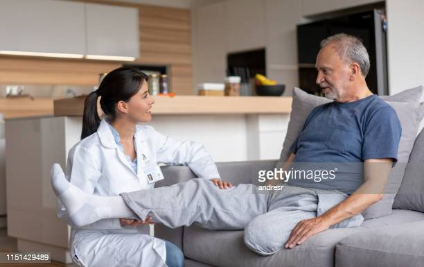 doctor making visiting a disabled senior patient at home - diabetic amputation stock pictures, royalty-free photos & images