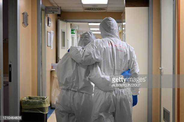 TOPSHOT Doctor Marco and nurse Manu wearing protective gear react at the end of their shift in a corridor of the level intensive care unit treating...