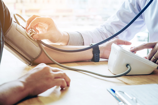 Doctor Measuring arterial blood pressure woman patient on arm Health care in hospital 867962636