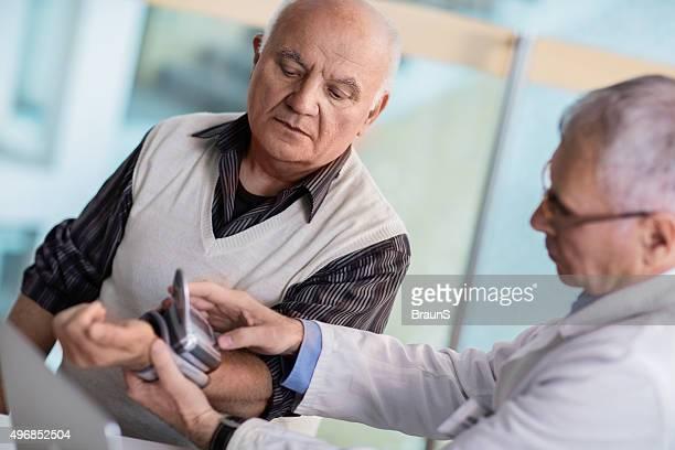 Médico medir a pressão arterial do Homem idoso.