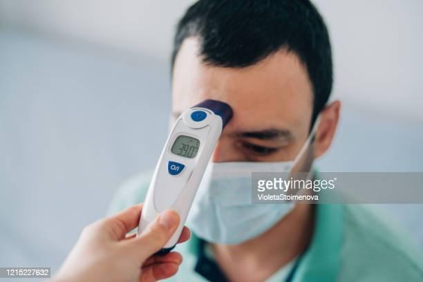 デジタル温度計で体温を測定する医師。 - digital thermometer ストックフォトと画像