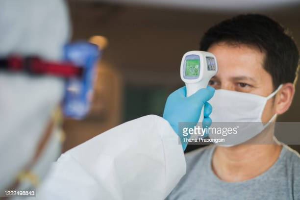doctor measuring body temperature with digital thermometer - digital thermometer ストックフォトと画像