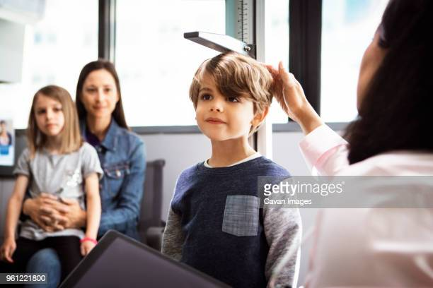 doctor measuring boys height while family sitting in clinic - patients brothers stock pictures, royalty-free photos & images