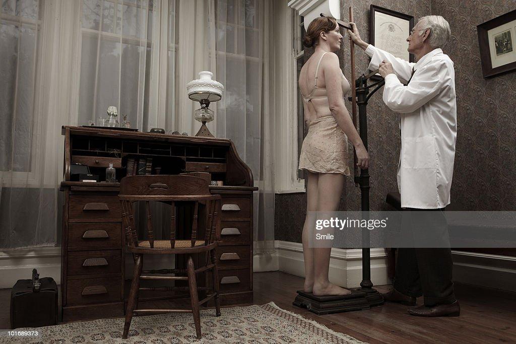 Doctor measuring female patient's height : Bildbanksbilder